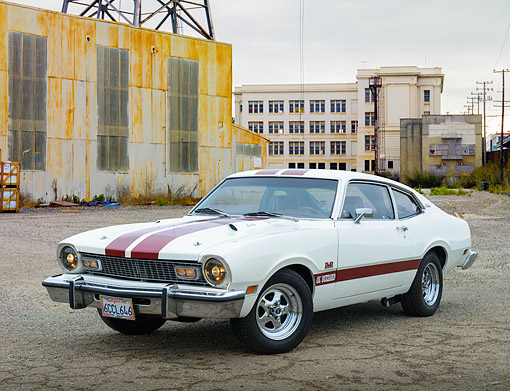 AUT 23 RK3458 01 © Kimball Stock 1974 Ford Maverick White With Red Stripes 3/4 Front View On Pavement By Old Factory Building