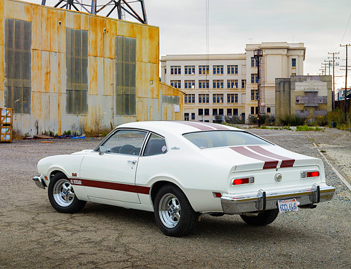 AUT 23 RK3459 01 © Kimball Stock 1974 Ford Maverick White With Red Stripes 3/4 Rear View On Pavement By Old Factory Building