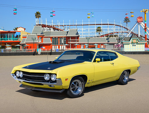 AUT 23 RK3470 01 © Kimball Stock 1970 Ford Torino 429 Cobra Jet Ram Air Yellow And Black 3/4 Front View On Pavement By Roller Coaster
