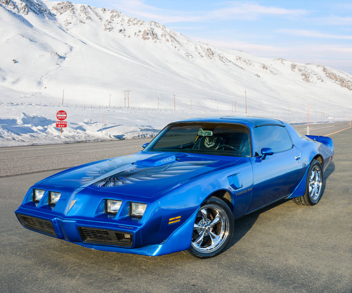 AUT 23 RK3472 01 © Kimball Stock 1979 Pontiac Trans Am 6.6 Liter Blue 3/4 Front View On Pavement By Snow Covered Mountains