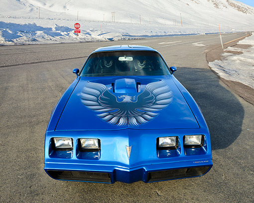 AUT 23 RK3473 01 © Kimball Stock 1979 Pontiac Trans Am 6.6 Liter Blue Front View On Pavement By Snow Covered Mountains