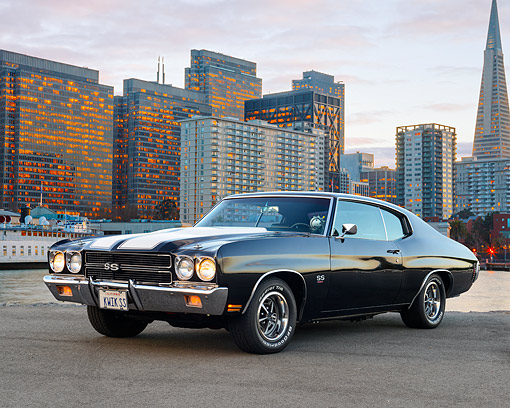 AUT 23 RK3520 01 © Kimball Stock 1970 Chevrolet Chevelle SS 454 Black With White Stripes 3/4 Front View On Pavement By City Buildings At Dusk