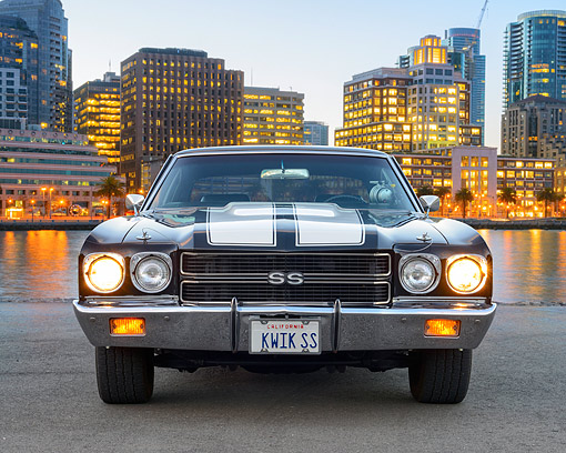AUT 23 RK3522 01 © Kimball Stock 1970 Chevrolet Chevelle SS 454 Black With White Stripes Front View On Pavement By City Buildings At Dusk