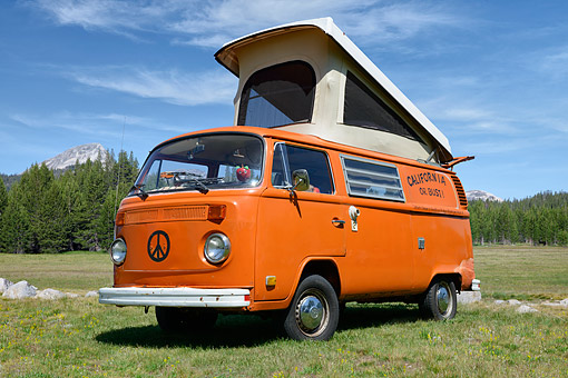 AUT 23 RK3532 01 © Kimball Stock 1975 Volkswagon Bus Campmobile Orange With Peace Sign On Grass By Mountain