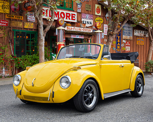 AUT 23 RK3704 01 © Kimball Stock 1972 Volkswagen Super Beetle Convertible Yellow 3/4 Front View By Gas Station Building