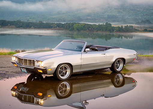AUT 23 RK3801 01 © Kimball Stock 1970 Buick Skylark Convertible Silver 3/4 Front View Surrounded By Water Puddle With Lake In Background
