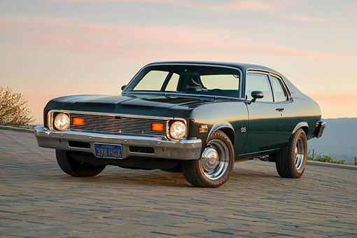 AUT 23 RK3802 01 © Kimball Stock 1973 Chevrolet Nova SS 350 Green 3/4 Front View On Cobblstone At Sunset
