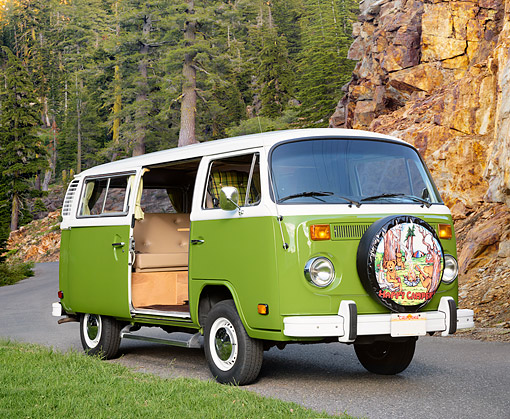 AUT 23 RK3809 01 © Kimball Stock 1973 Volkswagen Camper Bus Green 3/4 Front View On Road By Trees