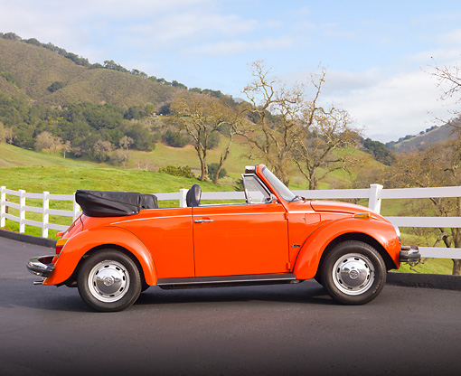 AUT 23 BK0004 01 © Kimball Stock 1974 Volkswagen Cabriolet Orange Peel Profile View On Pavement By White Fence And Hills