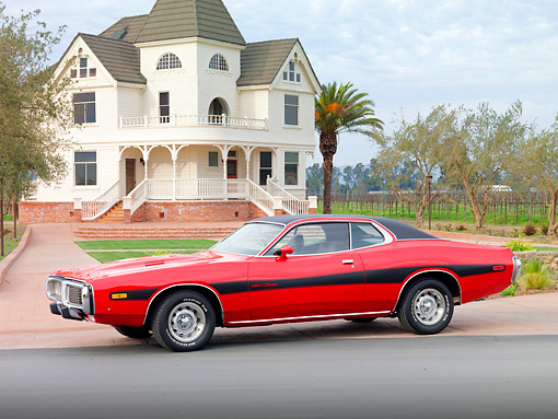 AUT 23 BK0007 01 © Kimball Stock 1973 Dodge Charger SE 440 Red With Black Stripe 3/4 Front View On Pavement By House