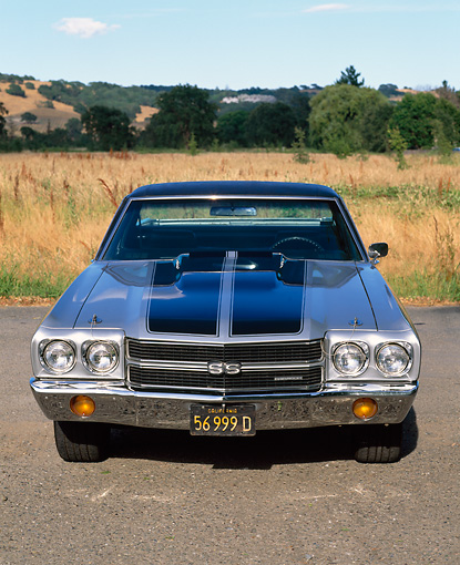 AUT 23 RK0039 02 © Kimball Stock 1970 Chevrolet El Camino SS 454 Silver Black Stripe Head On Shot On Pavement By Tall Grass Blue Sky