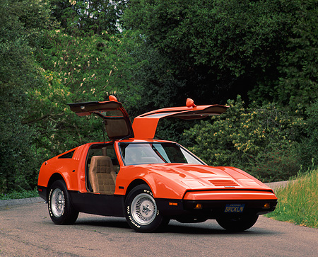 AUT 23 RK0076 02 © Kimball Stock 1975 Bricklin Orange And Black 3/4 Front View Doors Open On Pavement By Trees