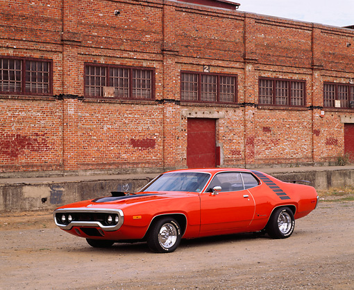 AUT 23 RK0089 03 © Kimball Stock 1972 Hemi Orange Plymouth Road Runner 3/4 Front View On Pavement By Brick Building