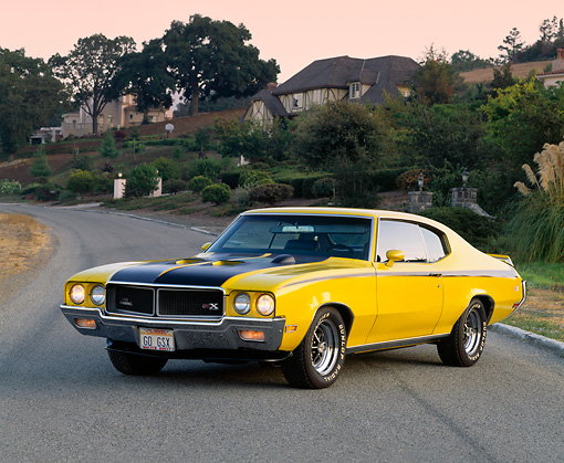 AUT 23 RK0116 02 © Kimball Stock 1970 Yellow Buick GSX 3/4 Front On Road Near Houses On Hill