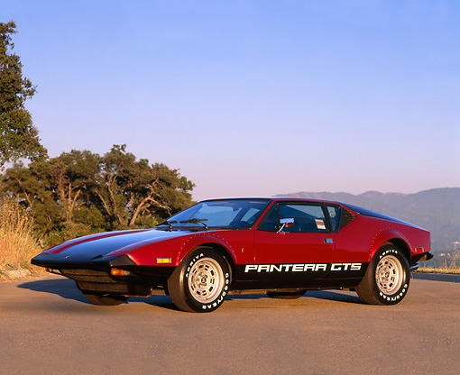 AUT 23 RK0124 06 © Kimball Stock 1974 De Tomaso Pantera GTS Maroon And Black 3/4 Front View On Pavement By Trees Mountains Blue Sky