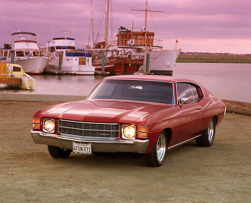 AUT 23 RK0191 07 © Kimball Stock 1971 Chevrolet Chevelle Red 3/4 Front View On Dirt By Harbor Headlights On