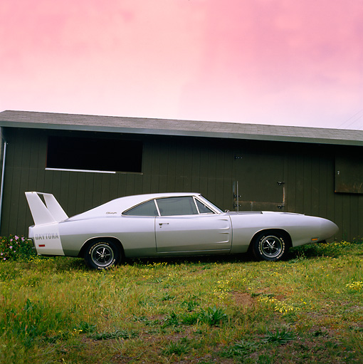 AUT 23 RK0221 04 © Kimball Stock 1970 Dodge Charger Daytona Silver Profile View On Grass By Building