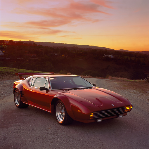 AUT 23 RK0244 01 © Kimball Stock 1972 De Tomaso Pantera Burgundy 3/4 Front View On Pavement Orange Sky At Sunset
