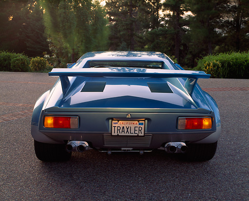 AUT 23 RK0271 01 © Kimball Stock 1971 De Tomaso Pantera Blue And Silver Rear View On Pavement Brake Lights On Trees Background