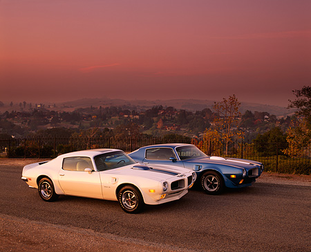 AUT 23 RK0280 02 © Kimball Stock 1970 & 1971 Pontiac Trans Am Blue And White 3/4 Side View On Pavement Dark Pink Sky
