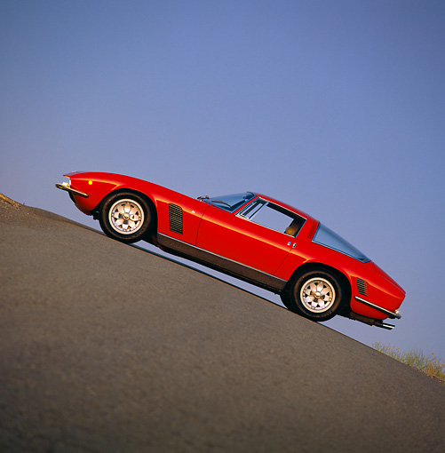 AUT 23 RK0306 05 © Kimball Stock 1971 Iso Grifo Red Slanted Side View On Pavement Hill Blue Sky