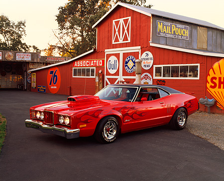 AUT 23 RK0379 01 © Kimball Stock 1972 Mercury Montego GT 429 Red With Flames 3/4 Front View By Barn