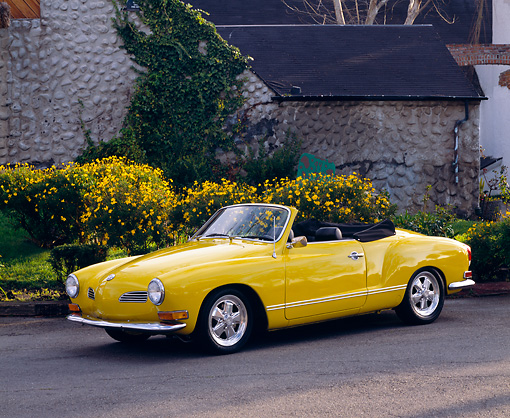 AUT 23 RK0411 01 © Kimball Stock 1971 VW Karmann Ghia Convertible Yellow 3/4 Side View On Pavement By House