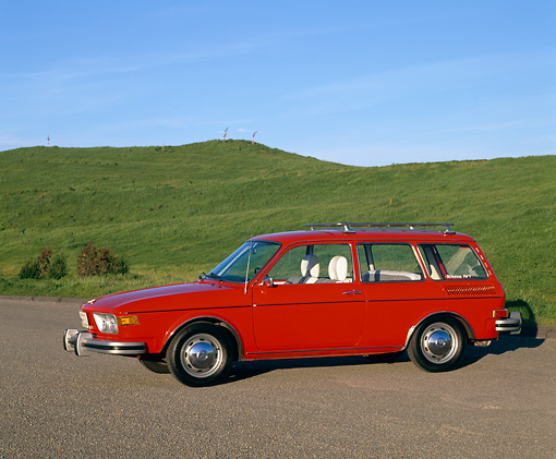 AUT 23 RK0416 01 © Kimball Stock 1974 VW 412 Estate Wagon Red Side 3/4 View On Pavement By Grass Hills Blue Sky