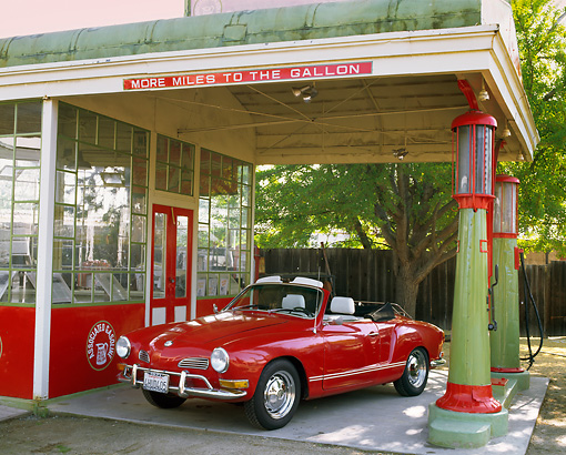 AUT 23 RK0417 01 © Kimball Stock 1971 VW Karmann Ghia Convertible Red 3/4 Front View By Old Gas Station