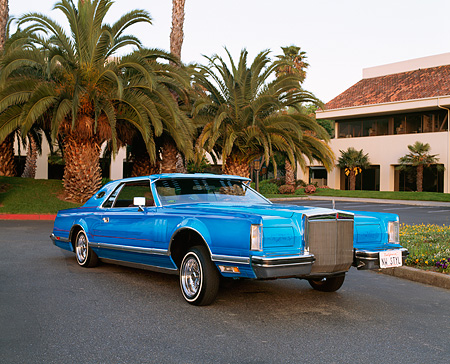 AUT 23 RK0432 01 © Kimball Stock 1979 Lincoln Continental Lowrider Blue Raised 3/4 Front View On Pavement By Palm Trees And Building