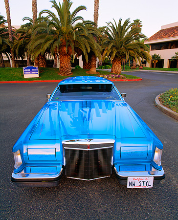 AUT 23 RK0434 01 © Kimball Stock 1979 Lincoln Continental Lowrider Blue Wide Angle Head On Shot On Pavement Palm Trees