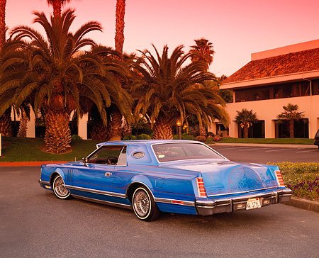 AUT 23 RK0436 06 © Kimball Stock 1979 Lincoln Continental Lowrider Blue 3/4 Rear View On Pavement By Palm Trees And Building Filtered