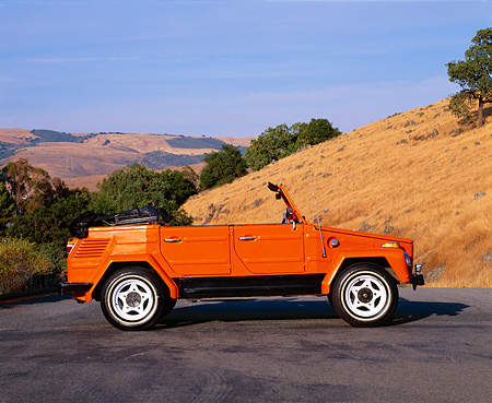 AUT 23 RK0442 01 © Kimball Stock 1973 Volkswagen Thing Type 181 Orange Profile On Pavement By Dry Grass Hills