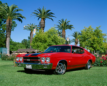 AUT 23 RK0452 03 © Kimball Stock 1970 Chevrolet Chevelle SS 454 Red And Black Stripe 3/4 Low Front View On Grass By Trees Blue Sky