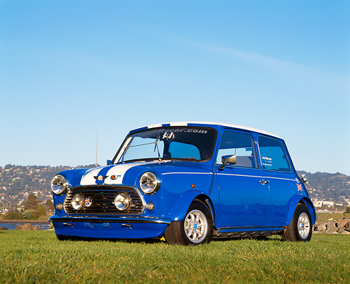 AUT 23 RK0490 02 © Kimball Stock 1974 Austin Mini Cooper Blue White Stripe Low 3/4 Front View On Grass Blue Sky