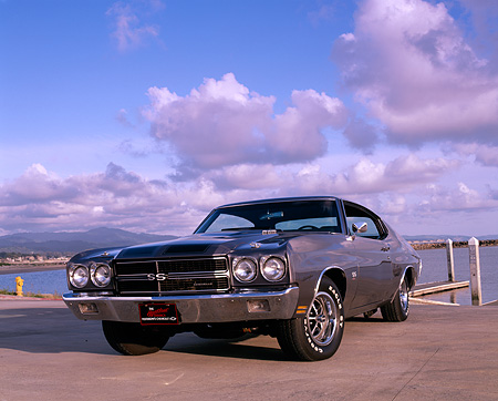 AUT 23 RK0550 02 © Kimball Stock 1970 Chevrolet Chevelle 454 SS Gray Black Low 3/4 Front View On Pavement By Water Clouds