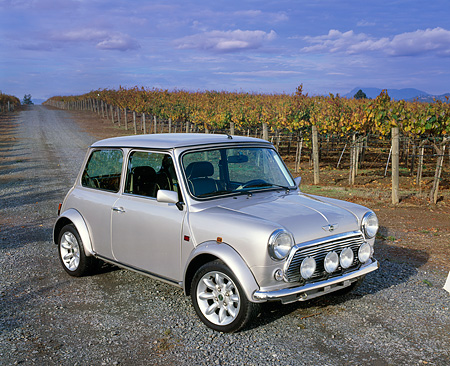 AUT 23 RK0666 05 © Kimball Stock 1971 Austin Mini Cooper Silver 3/4 Side View On Gravel By Vineyard