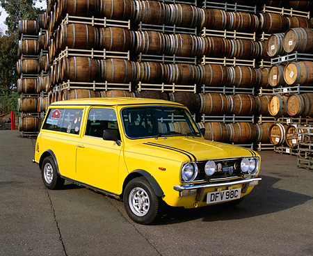 AUT 23 RK0682 05 © Kimball Stock 1970 Mini Estate Clubman Yellow 3/4 Front View On Pavement By Barrels