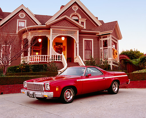 AUT 23 RK0811 02 © Kimball Stock 1975 Chevrolet El Camino SS Red 3/4 Front View On Pavement By House