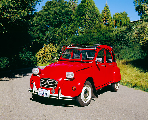 AUT 23 RK0848 02 © Kimball Stock 1973 Citroen 2CV Red 3/4 Front View On Pavement By Trees Blue Sky