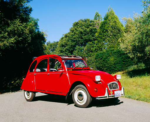 AUT 23 RK0849 01 © Kimball Stock 1973 Citroen 2CV Red 3/4 Front View On Pavement By Trees Blue Sky