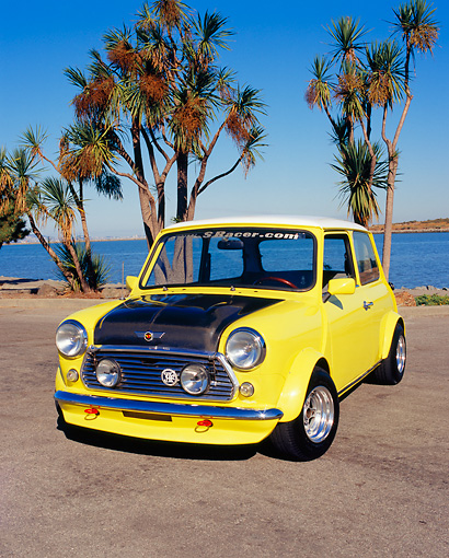 AUT 23 RK0869 01 © Kimball Stock 1971 Austin Mini Cooper S Racer Yellow 3/4 Front View On Pavement By Water