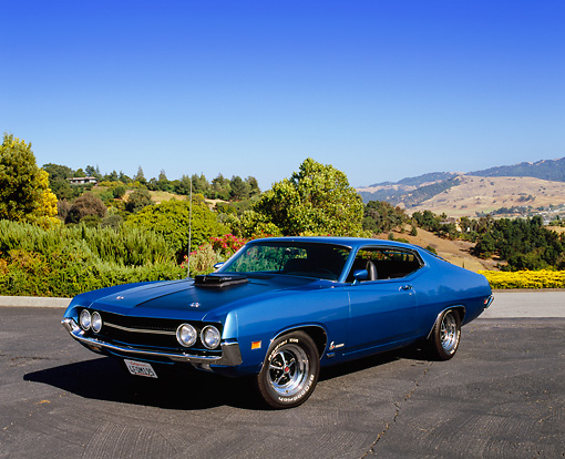 AUT 23 RK0942 05 © Kimball Stock 1970 Ford Torino Cobra SCJ Blue 3/4 Side View On Pavement By Trees