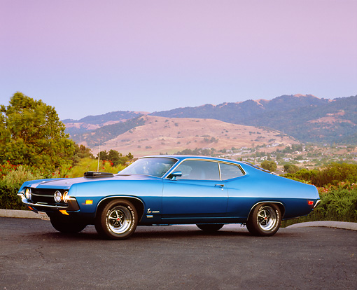 AUT 23 RK0947 02 © Kimball Stock 1970 Ford Torino Cobra SCJ Blue 3/4 Side View On Pavement By Trees At Dusk