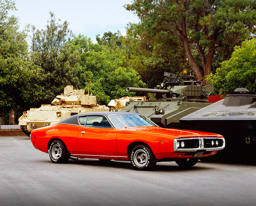 AUT 23 RK0952 03 © Kimball Stock 1971 Dodge Charger 500 Orange 3/4 Side View On Pavement By Military Tanks