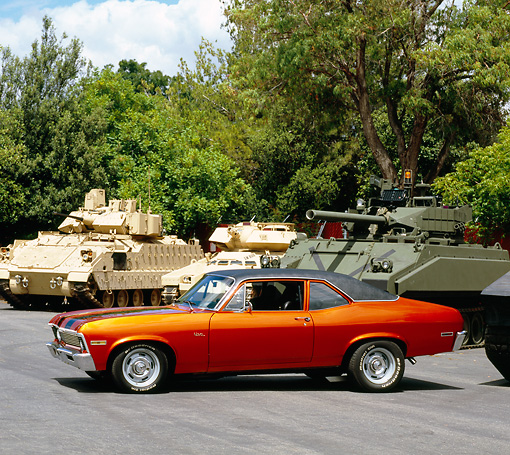AUT 23 RK0953 02 © Kimball Stock 1970 Chevy Nova Orange And Black 3/4 Side View On Pavement By Military Tanks