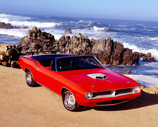 AUT 23 RK1002 06 © Kimball Stock 1970 Plymouth, Cuda Convertible, Orange Overhead 3/4 Front View On Sand By Ocean