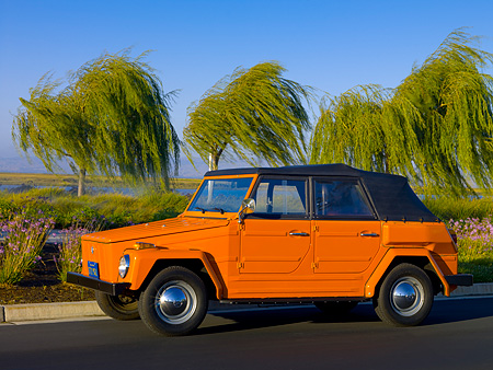 AUT 23 RK1055 01 © Kimball Stock 1974 Volkswagen Thing Type 181 Orange Low 3/4 Side View On Pavement By Trees