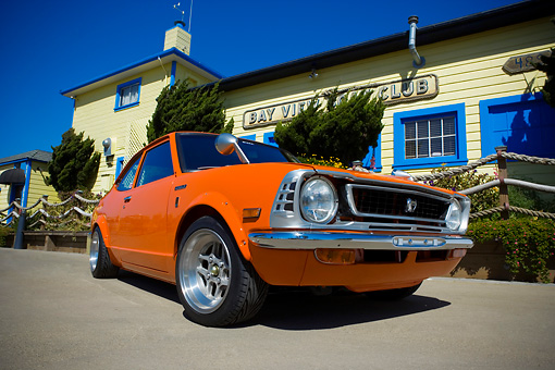 AUT 23 RK1101 01 © Kimball Stock 1973 Toyota Corolla Orange Low 3/4 Front View On Pavement