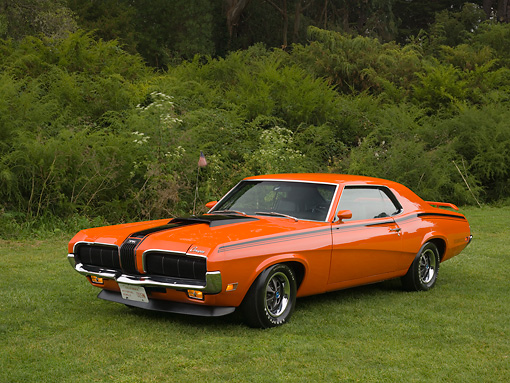 AUT 23 RK1122 01 © Kimball Stock 1970 Mercury Cougar Eliminator Orange 3/4 Front View On Grass Trees Background